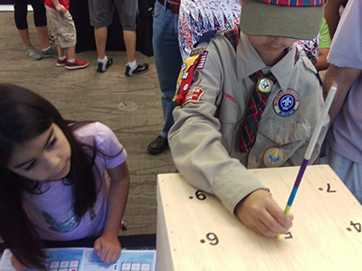 Visiting Scout uses a color-coded, calibrated stick to determine sea surface topography within a wooden box while his sister records his results by placing stickers on a card.
